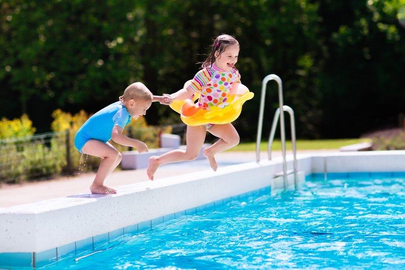 Cloro para Piscina - Duas crianças pulando em uma pisca de água azul